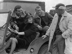 """American film actors Robert Wagner (left), Steve McQueen and English actress Shirley Anne Field in a Jeep Willys MB talking to director Philip Leacock on the set of """"The War Lover""""."""