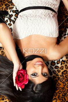 top view of a beautiful indian woman with a rose in her hair. - Top view of a beautiful Indian woman with a rose in her hair lying on back, Model: Stephanie Reddy