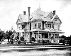 Exterior front corner view of the Victorian style residence of E.F.C.  Klokke at 2105 South Figueroa Street, Los Angeles. Small trees and  plants are seen, as well as a carriage house in the rear. The two-story wooden Victorian house has a covered wrap-around porch and  two broad stairways leading to the porch. A dome is perched on the  many-gabled roof. 1890