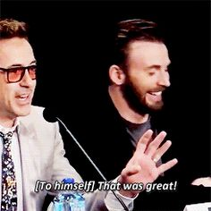 Chris Evans laughing at Robert Downey Jr's joke.