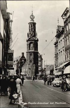 1948. View on the Reguliersbreestraat with Munttoren seen from the Rembrandplein. The Reguliersbreestraat is a street between the Rembrandtplein and the Kalverstraat. The street was named after the Regular Monastery (1394 - 1532) that was built on this location. The monastery was located outside the city walls and the Regulierspoort city gate of which the Munttoren tower is the only part that is left. #amsterdam #1950 #Reguliersbreestraat