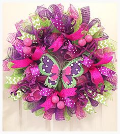 Do you enjoy BUTTERFLYS- Then this Butterfly Wreath will be perfect to hang in your home or on your covered front porch.  It is made with high quality purple, pink and lime deco mesh.  There are purple poke a dot ribbons with lime chevron ribbons and pink ribbons. Glittered purple picks with pink glittered balls have been placed all around the wreath.  It shows with a fun handcrafted wooded Butterfly that has been cut out with 2 pieces of wood, painted purple, pink and lime and shows with…