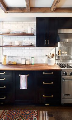 Dark kitchen, white subway tiles and brass handles