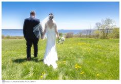 Anna and Chris walking along in a field during their Point Lookout, Northport Maine wedding.