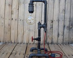 Industrial pipe table lamp made of galvanized fittings and pipes with two e27 vintage lamps. Painted with primer and iron-spray. Weight: 5kg  Dimensions: Length 28cm / Height 28cm / Width 16cm  Delivery time: 7-10 days (in Greece)  * Our recommendation is to use lamps that have no more than 40W
