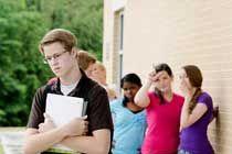 Un adolescente apenado se aleja de otras adolescentes que lo acosan.