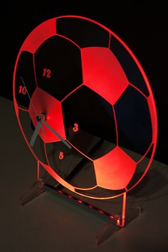 Clock with red backlight LED in the shape of a football. New design.