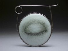 "Jessica Calderwood, ""Blink"" (back view), enamel, copper, sterling silver, stainless steel, 2.5"" x 2.5"", 2007"