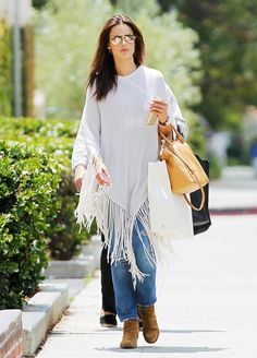 Alessandra Ambrosio wears a white fringe poncho by Minnie Rose, jeans, Saint Laurent suede boots, and a Michael Michael Kors satchel