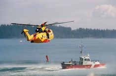 A Royal Canadian Air Force (RCAF) CH-149 Cormorant SAR helicopter hoists a man from a Canadian Coast Guard (CCG) vessel.