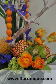 Bright orange wedding flowers with green and blue accent flowers and hanging kumkwart for a wedding centerpiece