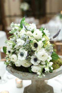 the brides bouquet is beautifully displayed on a mossed concrete pedestal placed on the sweetheart table for all the guests to enjoy! semi structured bridal bouquet of white hydrangea, mini green hydrangea, lavender scabiosa, white stock, white ranunculus, lavender, white scabiosa,white anemone, lavender & lemon leaf wrapped in cream satin ribbon