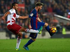 Lionel Messi of FC Barcelona is tackled by Mathieu Fernand of Granada during the La Liga match between FC Barcelona and Granada at Camp Nou stadium...