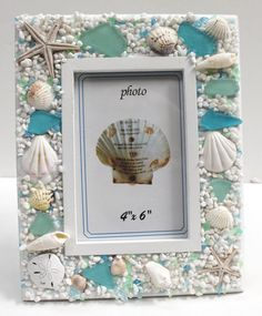 White picture frame decorated with blue and green seaglass & seashells holds a 4x6 photograph