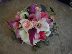 Purple Anthiriums, Pink Anthiriums, White Calla Lilies, Soft Pink Calla Lilies, Soft Pink Roses and Eucalyptus Seed accents.