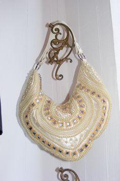 Üppige, aufwendig gestaltete cremefarbene Perlentasche in extravaganter Form aus Satin.   Sie wird mit einem Druckknopf geschlossen und verfügt übe...