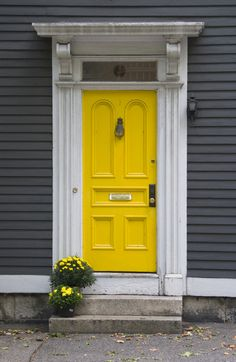 seriously considering this color combo. yellow door and gray exterior.