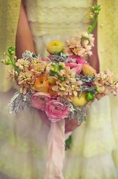 WaterColors - a Vows, Estes Park Original. We absolutely ADORE this bouquet... it looks like it is direct from an artist's palette! Pale ranuculous in pale yellows, peaches and pinks with pale peach stock,dusty miller and minimal greenery makes this a must have for anyone looking for a Vintage look!
