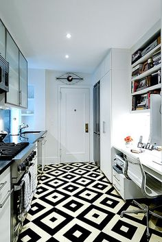 Diamond pattern black and white tile floor in a small New York City apartment galley kitchen.  Awesome floor in white kitchen. Like the writing desk in the kitchen too!