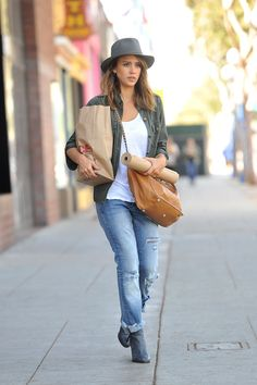 Jessica Alba wears a green shirt, white singlet, jeans and grey boots