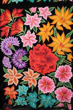 Lienzo con bordado de diversas flores, hecho a mano con aguja sobre tela de raso negra.