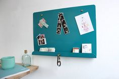 A sheet steel magnetic noticeboard designed to help keep a little more order in today's busy society.Available in Water Blue, Purple Red, LDF Red, Lemon Yellow and Heather VioletMade by hand in Sheffied (the Steel City), each board is cut and folded to the required dimensions with the front lip and brass hanger providing the ideal space for your keys, wallet or any other important items. The boards are produced in small batches and come with three golden spherical magnets to get you started…