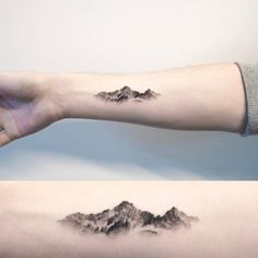 Mountain tattoo on the right inner forearm.