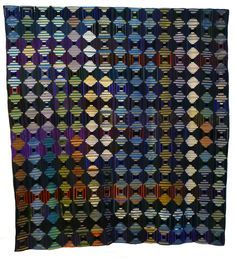 1880 - 1889.  This log cabin coverlet uses the 'Courthouse Steps' block variation made from strips of richly coloured velvet, silk and ribbons . The blocks are all hand-pieced onto cotton foundation squares which have been over sewn together. It was made by Frances Haseldien, the daughter of a Fish merchant in Workington, Cumbria. 204cm x 209cm