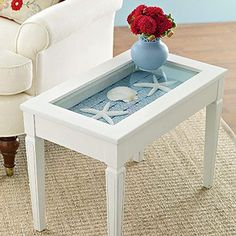 White glass-topped side table with shells