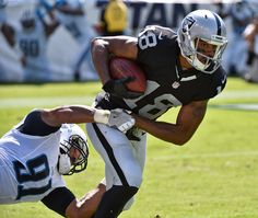 Andre Holmes #18 of the Oakland Raiders is tackled by Derrick Morgan #91 of the Tennessee Titans during the first half at Nissan Stadium on September 25, 2016 in Nashville, Tennessee.  (Photo by Frederick Breedon/Getty Images)