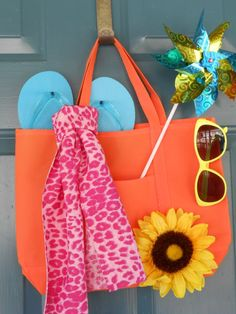 """Summer """"wreath"""" for front door. Everything came from the dollar store, a simple beach tote (kept folded flat), flip flops, scarf, sunflower, pinwheel and sunglasses. Arrange as desired and hot glue parts in to place and you're done!"""