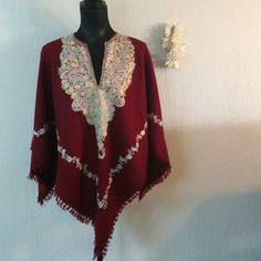 Gorgeous embroidered poncho. This is really cool. It's a deep burgundy red with pastel floral embroidery. It's fully lined and has fringe along the edges. Perfect condition.  The tag (which I've lost) said it was made in Carmel California out of fine wool. It will fit a wide range of sizes.  For sizing reference it's on a small 4-6 mannequin. Boutique Jackets & Coats Capes