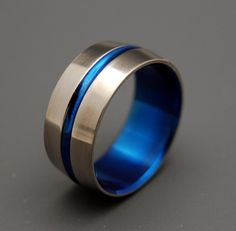 I believe this is the one he has settled on. I found it on Etsy, which is unbelievable since it came from a google search to begin with. ALL Titanium with a blue inside and blue strip through the middle.