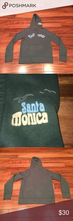 """Hollister """"SANTA MONICA"""" hoodie Size XL. Olive with light blue and cream writing. HOLLISTER written across the chest and SANTA MONICA with the HOLLISTER bird logo on the left side of the hood (left when on wearer). Front pocket. Two buttons at top of neck and drawstring closure. 60% cotton and 40% poly. In EUC. Feel free to ask me any other questions😊 Hollister Tops Sweatshirts & Hoodies"""