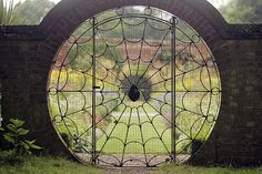 spiderweb gate, set in a stone wall. future house, yes! :)