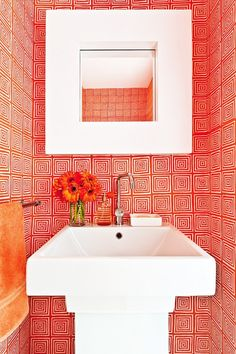 Bathroom with red and white geometric wallpaper.