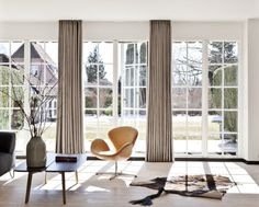 Modern mix in the summer cottage. Swan chair by Arne Jacobsen and vase from Kähler. Big windows and light fabric.