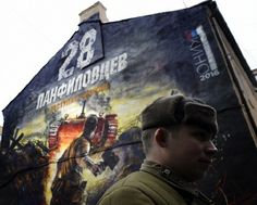 A man dressed in a Red Army's World War Two uniform takes part in the opening of a street art-style painting promoting the new Russian film 'The Panfilov 28' on a building in central Moscow on November 24, 2016. — AFP pic