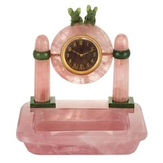 Art Deco Rose Quartz and Nephrite Desk Clock  The rose quartz clock centering a circular pink guilloche dial with gold Arabic numerals, topped by two carved nephrite dogs, supported by two rose quartz pillars with nephrite rings and square platforms, the rounded rectangular rose quartz base with recessed interior serving as a dish