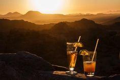 Auf der 16-tägigen Mietwagenrundreise von Karawane Reisen gibt es auch zwei großartige Sundowner-Spots: Im Mowani Mountain Camp bei Twyfelfontein richtet sich der Blick direkt auf die atemberaubende Landschaft bis hin zur Steinwüste. Eine kleine Bar versorgt einen ausreichend mit Getränken. Im Okaukuejo Camp im Etosha Nationalpark blickt man hingegen auf das beleuchtete Wasserloch, an dem sich in der Abenddämmerung so manche Tiere tummeln.