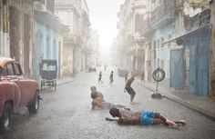 Havana weather in July and August counts as brutally hot. Short but heavy rains are very common and welcomed by locals, especially kids. (© Val Proudkii, USA, 2013 Sony World Photography Awards)