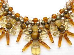 Tuca Stangarlin. Xamã de Outono 1. Colar terminado em fio de vidrilho, Medindo aproximadamente 46 cm de circunferência + Extensão; murano, pérola, olho de tigre e cristal tcheco. Acabamento folheado a ouro.