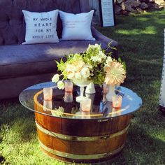 Lounge area with custom embroidered pillows, custom wine barrel coffee tables and milk glass compote centerpieces by AZ floral design.