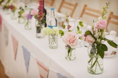 Wedding bunting is great decor for tables. Want to mock this look? We rent out misc. glass bottles and could do custom bunting.