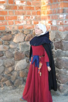 Outfit from th turn of 14th and 15th century. It consists of: linen chemise, linen underdress (cotte simple with buttoned sleeves), woolen overdress (so called 'Christine de Pisan's gown') with partially shortened and open sleeves, linen veil, woolen hood with lining, woolen cloak, woolen hose, period leather shoes, belt and garters. All fabrics 100% natural, all parts completly hand-sewn.