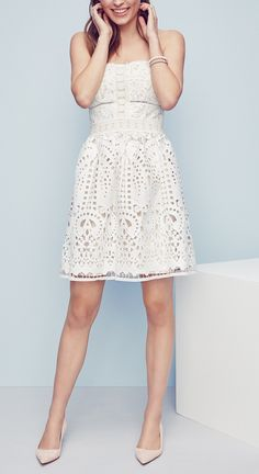 Just in time for spring and summer! This perfect little white party dress is crafted from gorgeous crochet lace and features a fitted strapless bodice with ladder stitching and floral trim.
