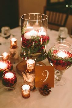 Red and white winter-inspired centerpiece for the holidays. Glass hurricane holders with cranberries and greenery surrounded by birch wood, silver votives, and pinecones. Willowdale Estate, a weddings and events venue north of Boston, Massachusetts WillowdaleEstate.com