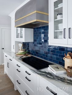 An indigo subway tile backsplash feels British and historical, and picks up on the deep veining in the Calacatta marble countertops. | Photographer: Janet Kimber | Designer: Colin Blanchard and Kenneth McRobbie