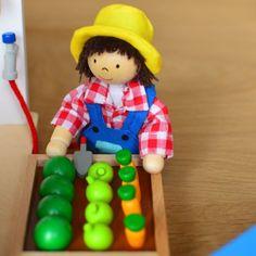 Une serre miniature en bois et en plexiglas, des petits jardiniers articulés, des outils et de beaux légumes à récolter dans un panier en osier. #Goki #JouetsEnBois #Miniature