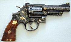 """Smith & Wesson Engraved Pre Model 29 .44 magnum blue finish 4"""" barrel full coverage engraving with multiple raised gold animals and 24K gold wire inlay that Alvin White was known for. Also checkered service stocks. This revolver was completed in 1957"""